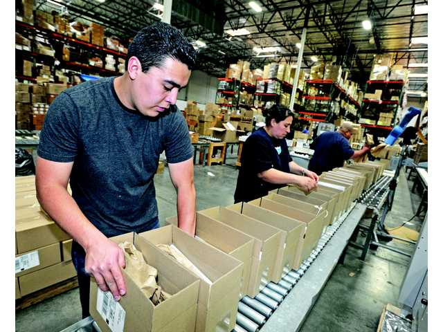 Employees of AMS Fulfillment package products to fill orders and ship them out. Within six months the company is already recovering from the loss of a major client.