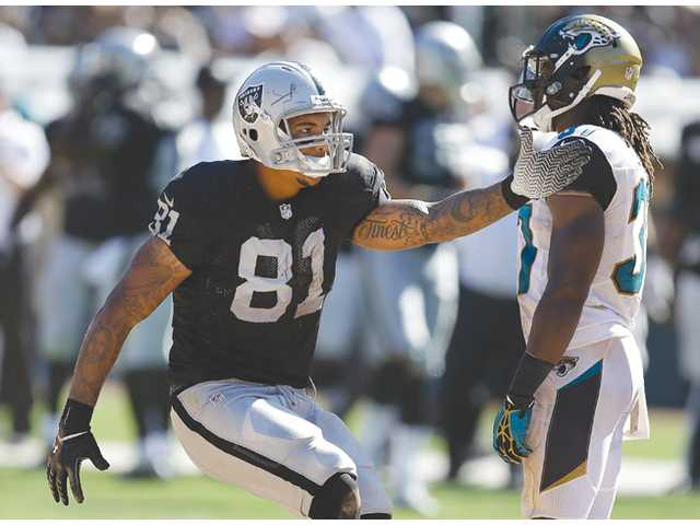 Oakland Raiders tight end Mychal Rivera (81), a former College of the Canyons player, signals first down against the Jacksonville Jaguars on Sunday in Oakland.