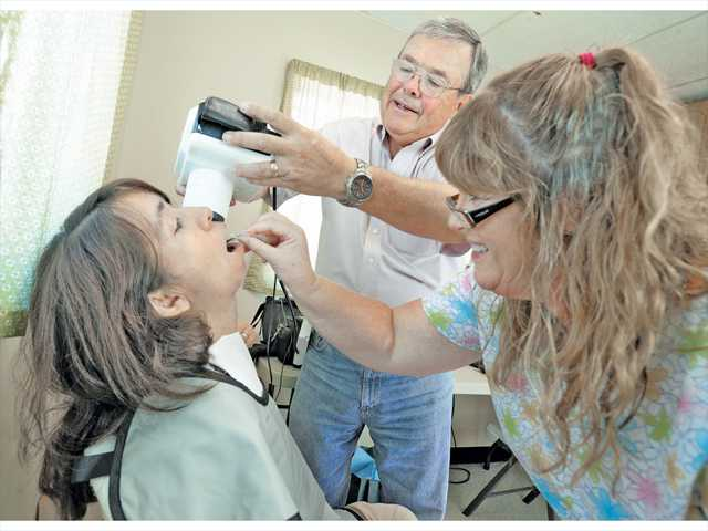 Patient Virginia Rea, left, gets an X-ray of her teeth by Tim Davis, center, and Dawn McNeil at the free dental clinic held at Bridge to Home in Saugus on Saturday. Photo by Dan Watson.