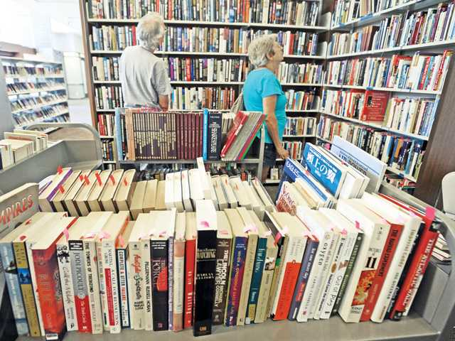 "Bob and Janice Ponek of Valencia search the hundreds of books on sale during the Friends of Santa Clarita Public Library ""Bag Sale"" at Newhall Library on Tuesday. Signal photo by Dan Watson"