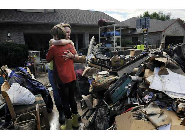 Homeowner Chris Ringdahl, left, is comforted by family friend Katherine MacIntosh, right, in front of her possessions as they cleanup from the floodwaters in Longmont, Colo., on Monday.