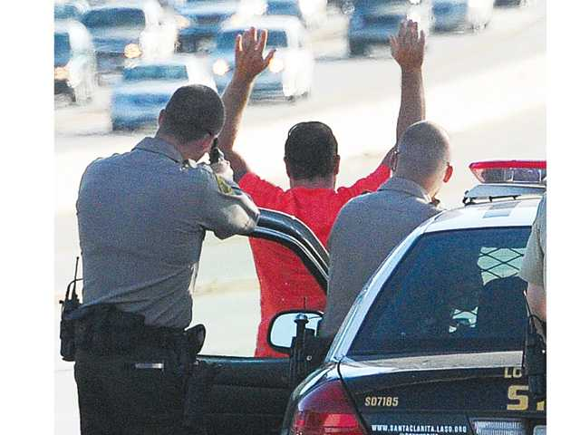 One of the male suspects puts his hands in the air after a traffic stop on Highway 14 near Newhall Avenue on Tuesday afternoon.