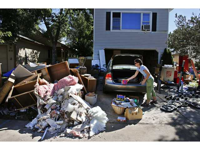 Shanda Roberson disposes of destroyed items from her home, after recent floods swept through Longmont, Colo. on Wednesday.