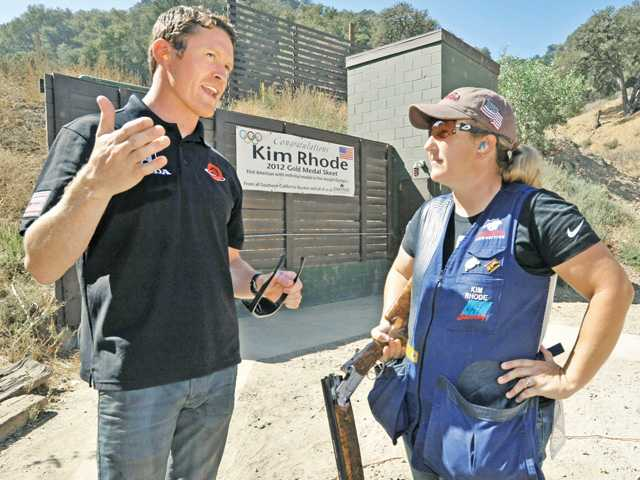 Two-time IndyCar champion Scott Dixon, left, gets instruction in skeet shooting from five-time Olympic shooting medalist Kim Rhode at Oak Tree Gun Club in Newhall on Wednesday. Signal photo by Dan Watson.