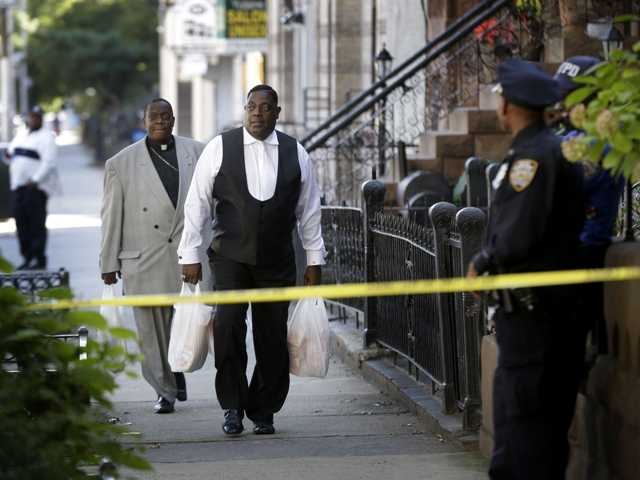 Bishops Gerald Seabrooks, right, and Willie Billips bring groceries to the home of Cathleen Alexis, mother of Washington Navy Yard gunman.