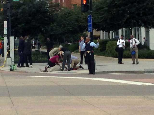 In this photo, which The AP obtained from Don Andres, shooting victim Vishnu Pandit is assisted on the sidewalk after coworkers took him by car from the Washington Navy Yard to receive medical attention Monday in Washington.
