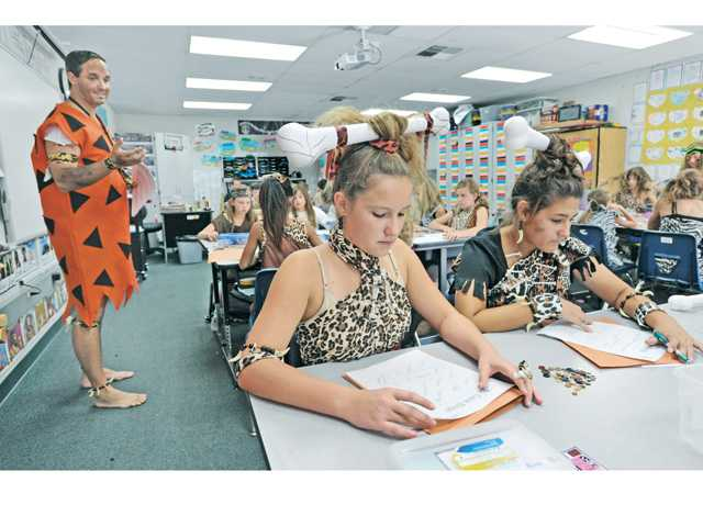"Sixth-grade teacher Bryan Eifert, left, wearing a Fred Flintstone costume, leads a class of sixth-graders dressed in the garb of early humans as they play ""caveman bingo"" with words relating to the study of Cro-Magnon man during Cro-Magnon Day at Pico Canyon Elementary School in Santa Clarita on Thursday.  Photo by Dan Watson."