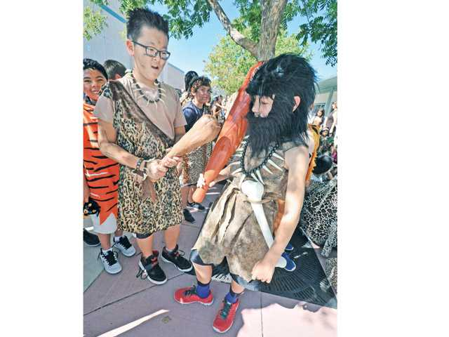 Sixth-graders Brian No, left, and Travis Schoelen wait for lunch dressed in the garb of early humans, including clubs and full beards, during Cro-Magnon Day at Pico Canyon Elementary School in Santa Clarita on Thursday. Photo by Dan Watson.