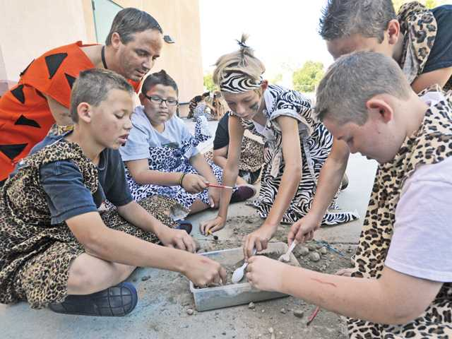 "Sixth-grade teacher Bryan Eifert, left, wearing a Fred Flintstone costume, assists a ""clan"" of sixth-graders dressed in the garb of early humans as they dig for artifacts as archeologists would. Photo by Dan Watson."