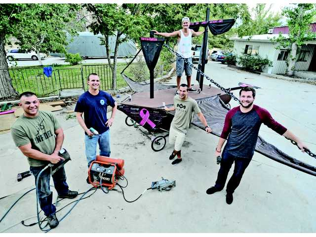 "From left, Cody Katz, Garrett Holcombe, Ryan Holcombe (on boat), Anthony Goldner and Jon Loch stand in front of the human-powered flying craft named ""Shellie Baby"" they built for the Red Bull Flugtag competition on Saturday. Signal photo by Dan Watson."