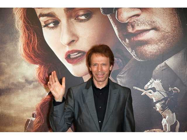 "In this July 24, 2013 file photo, Producer Jerry Bruckheimer poses for photographers as he arrives at the cinema for the French premiere of ""The Lone Ranger,"" in Paris, France. The Walt Disney Co. announced Thursday, Sept. 19, 2013, that it would not renew its first-look deal with the producer, when it expires next year."