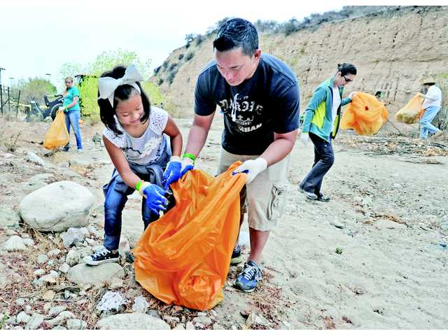 Makena Cua , 9, and her dad Jon join hundreds of volunteers who picked up trash in the Santa Clara riverbed near the Newhall Community Center in Newhall on Saturday. Signal photo by Dan Watson.