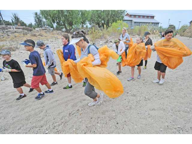 A group from Legacy Christian Academy join hundreds of volunteers who picked up trash  in the Santa Clara riverbed near the Newhall Community Center in Newhall on Saturday. Signal photo by Dan Watson.