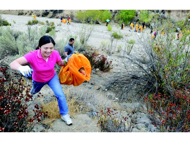 Kelly Wong climbs up the bank of the riverbed as she joins hundreds of volunteers who picked up trash in the Santa Clara riverbed near the Newhall Community Center in Newhall on Saturday. Signal photo by Dan Watson.