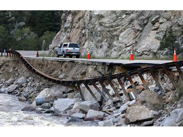 A guardrail hangs away from a closed canyon road, where some local residents are allowed to drive with caution, on Friday in Boulder, Colo.