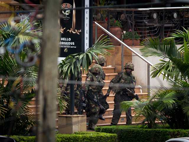 Soldiers from the Kenya Defense Forces carry a wounded colleague, following the sound of explosions and gunfire, out of the Westgate Mall in Nairobi, Kenya on Sunday.