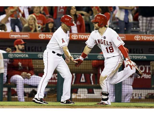 Los Angeles Angels' Collin Cowgill, right, is congratulated by coach Dino Ebel while rounding the bases on a solo home run against the Seattle Mariners in Anaheim on Saturday.