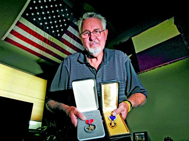 Vietnam veteran Bill Reynolds shows two of his medals — a Bronze Star and a Purple Heart — at his home in Valencia.