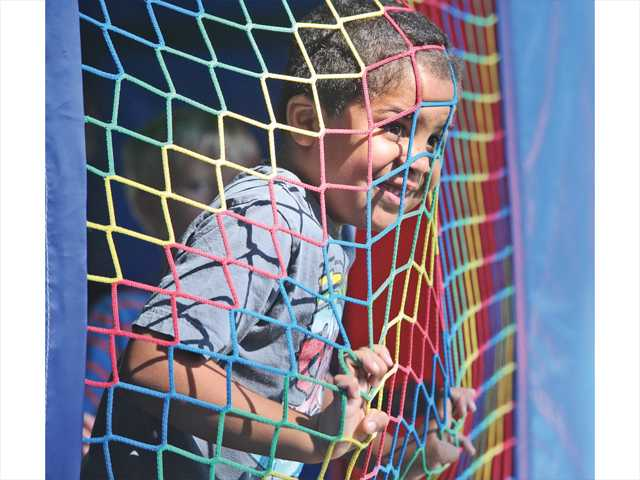 Raymond Mitchell, 5, of Saugus looks out through the netting of an inflatable bounce house at the Day For Kids event held at Newhall Park on Saturday. Photo by Dan Watson.