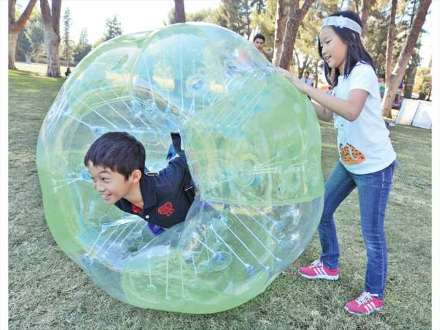 Celine Chen, 6, rolls her brother Jason, 7, in and inflatable ball at the bumber ball game at the Day For Kids event attended by hundreds of kids and their families held at Newhall Park on Saturday. Photo by Dan Watson.