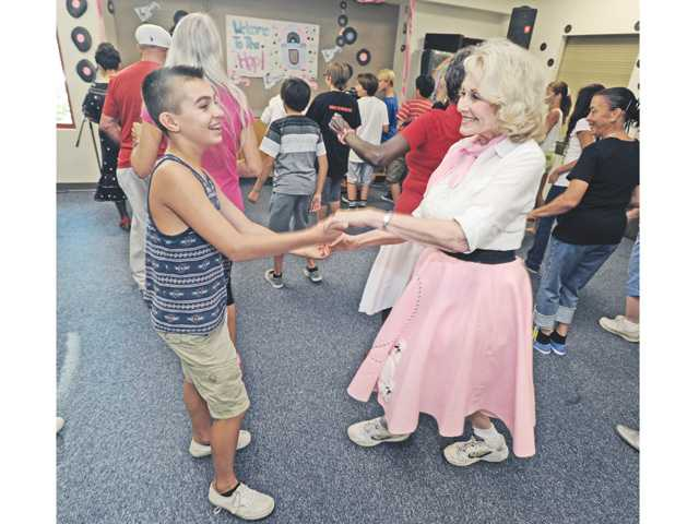 Castaic Middle School student Nathan Woodings, left, gets a dance lesson from Jan McBride during a Grandparents Day sock hop celebration at the Castaic Sports Complex on Friday. Signal photo by Dan Watson