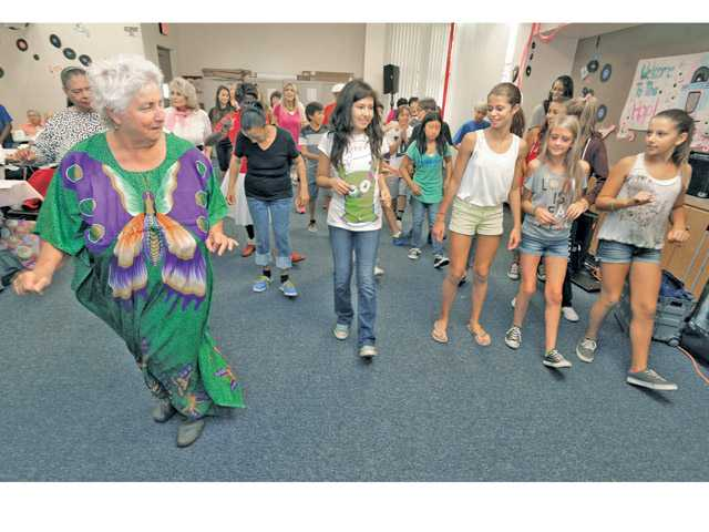 Castaic Middle School students follow the line dance instructions of Babette Singer, left, as they dance during the Castaic Sports Complex Grandparents Day event Friday. Signal photo by Dan Watson