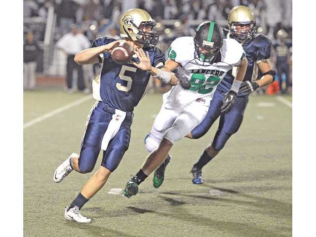West Ranch quarterback Chase Killingsworth, left, looks to pass as he outruns Thousand Oaks defender at Valencia High on Friday.