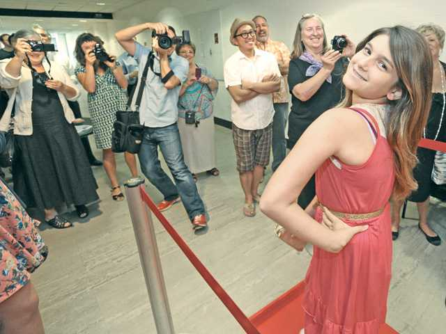 "Student filmmaker Rachel Greenleaf, 11, right, poses for the cameras on the red carpet as she enters the Bijou Theater for the premiere of the film she worked on, ""Quenched,"" at California Institute of the Arts in Valencia on Saturday. Photo by Dan Watson"