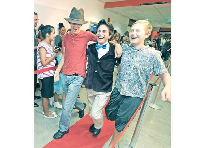 "Student filmmakers, from left, Zakariah O'Mara-Mezzano, Sean Arison and Cole Pitner enter the Bijou Theater from the red carpet for the premiere of their film ""Vasquez"" at California Institute of the Arts in Valencia on Saturday. Photo by Dan Watson"