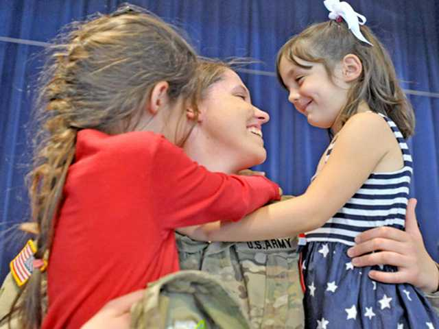 Pfc. Emily Dauer, 20, center, hugs her sisters, Skyler Hewitt, 7, and McKenna Hewitt, 6, in the multi-purpose room at Rosedell Elementary School on Monday. Photo by Charlie Kaijo.