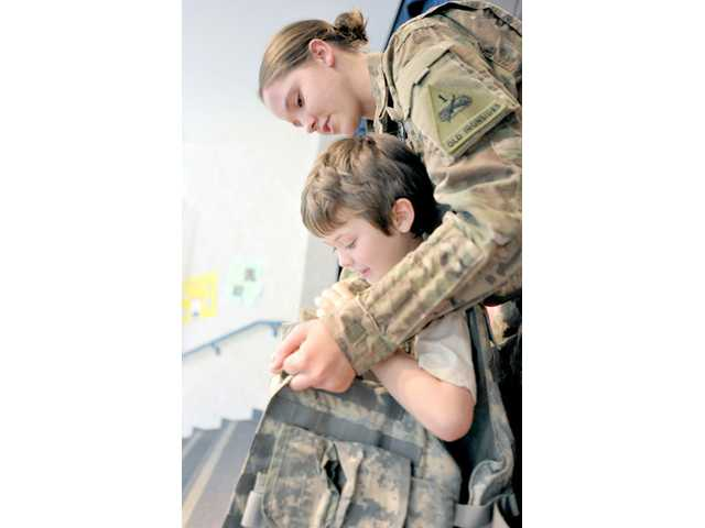 Pfc. Emily Dauer helps Wyatt Hawk, 7, put on an army combat vest on Monday during a presentation on her experiences in Afghanistan. Photo by Charlie Kaijo.