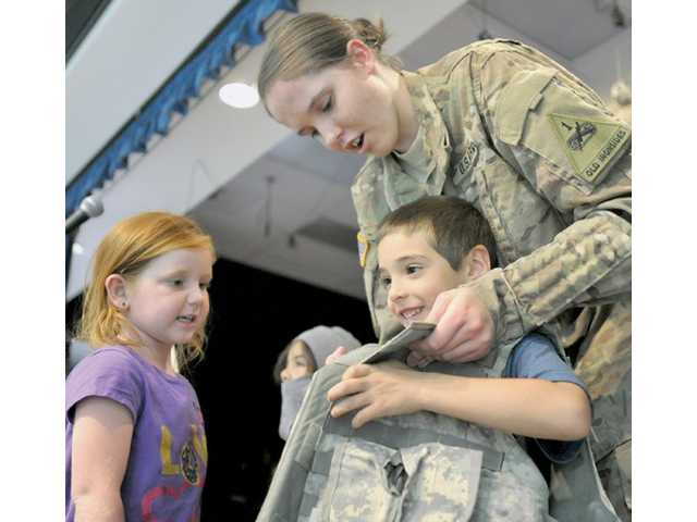 Pfc. Emily Dauer, 20, shows students at Rosedell Elementary School how to try on an Army combat vest during a presentation she gave Monday about her experiences in Afghanistan. Dauer is on active duty until 2018 and will serve in the Army reserves until 2020. Photo by Charlie Kaijo.