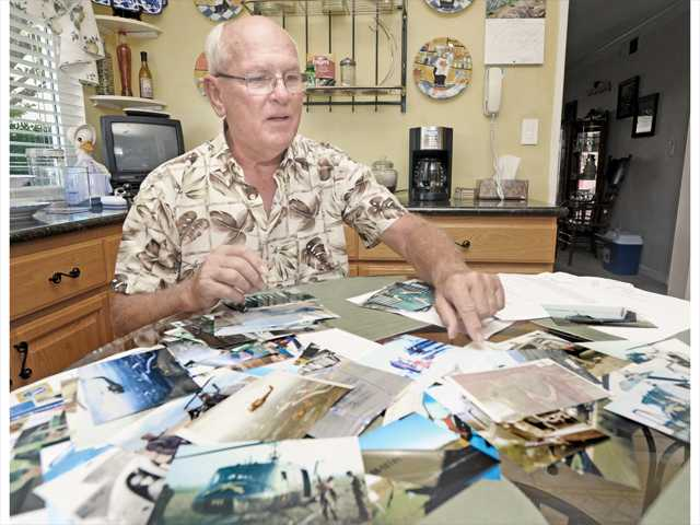 Vietnam war veteran Thomas Jones displays war era photos on his kitchen table. Photo by Dan Watson.