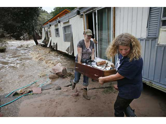 Water rushes through her destroyed home as resident Holly Robb, left, and her neighbor Pam Bowers salvage belongings in Lyons, Colo on Sept. 13.