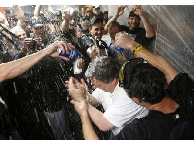 The Pittsburgh Pirates douse traveling secretary Greg Johnson with champaign and beer on Monday in Chicago after the Pirates clinched their first playoff berth in 21 years.
