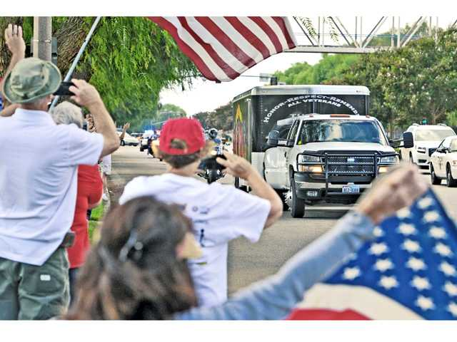 A small group waves flags on Magic Mountain Parkway as the trailer caring the American Veterans Traveling Tribute Vietnam Memorial Wall approaches the Westfield Valencia Town Center Mall on Wednesday where the wall will be displayed until Sunday. Signal photo by Dan Watson