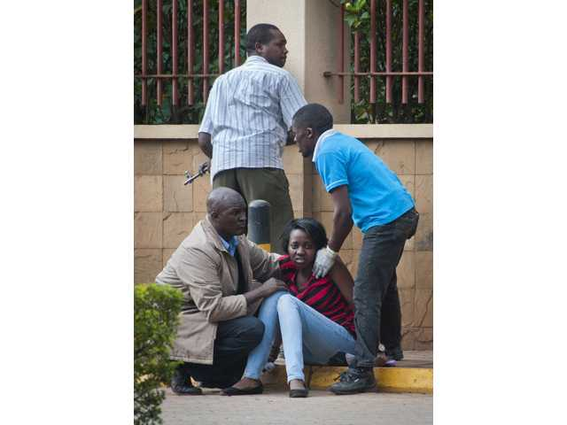 In this Saturday, Sept. 21 photo, a woman who had been hiding inside and managed to flee sits in a state of shock, as an unidentified armed member of the security forces, above, keeps watch outside the Westgate Mall in Nairobi, Kenya following an attack by armed Islamic extremist group al-Shabab.