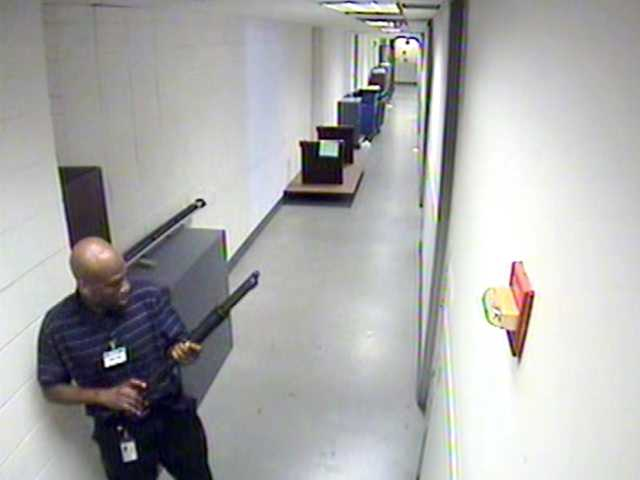 This image from video provided by the FBI, shows Aaron Alexis moves through the hallways at the Washington Navy Yard on Sept. 16, carrying a Remington 870 shotgun.