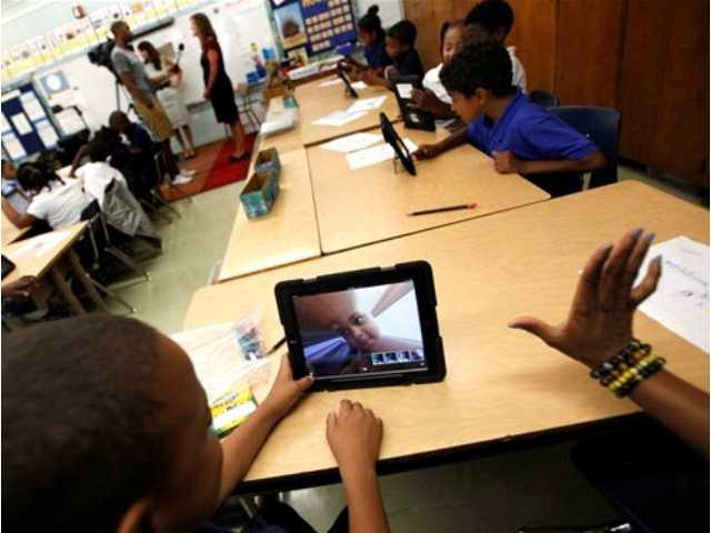 In this Aug. 27, 2013, file photo, students photograph themselves with an iPad during a class at Broadacres Elementary School in Carson, Calif. Los Angeles school officials have halted home use of iPads after nearly 300 students at Roosevelt High made quick work of hacking through security so they could surf the Internet and access social media sites.