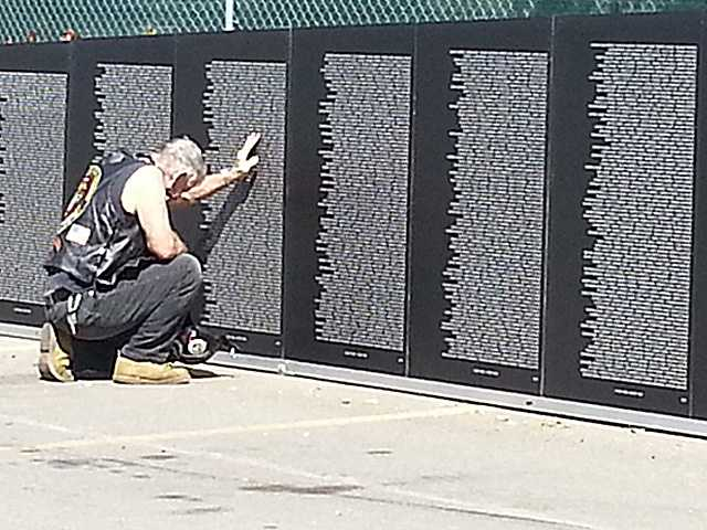 A visitor to the AVTT Traveling Vietnam Memorial Wall at the Westfield Valencia Town Center finds the name of a loved one Thursday. A dedication ceremony is scheduled at 6 p.m. Thursday. Mallory Fencil/For The Signal