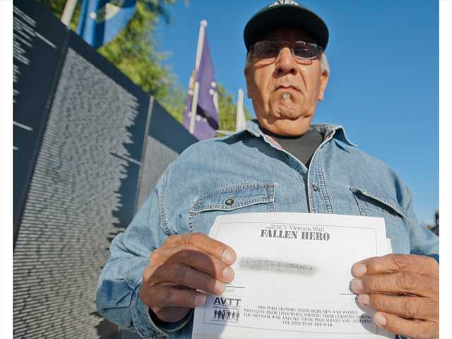 Leroy Martinez, holds a rubbing of his cousin's name from the wall. His cousin, Earnest Perez, was 20 when he was killed. Photo by Charlie Kaijo.