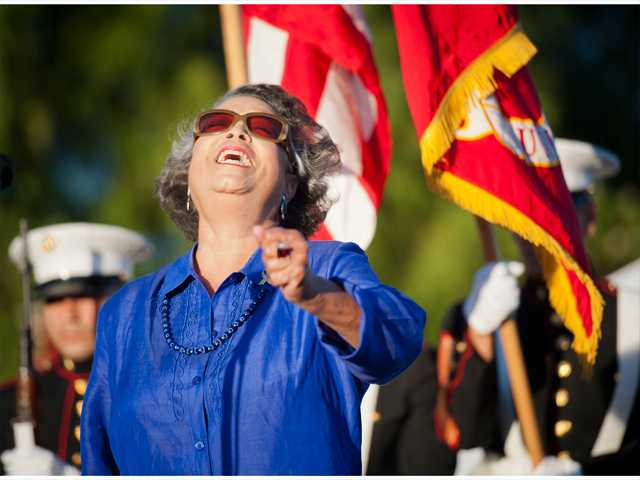 Guest singer Gayle LaRone sings 'America the Beautiful' in front of the color guard at the Traveling Vietnam Memorial Wall at the Westfield Valencia Town Center on Thursday. Photo by Charlie Kaijo.