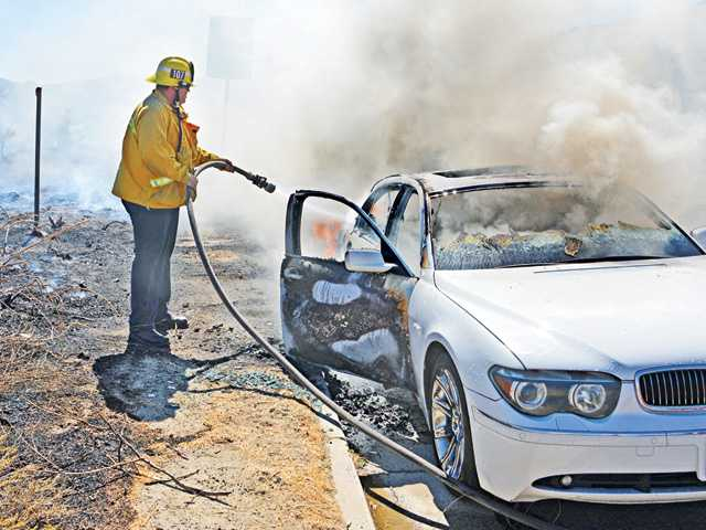 Firefighters quickly contained a fire involving a BMW vehicle on Sierra Highway about a quarter-mile south of Golden Valley Road in Newhall Friday afternoon. Photo by Rick McClure/For The Signal.