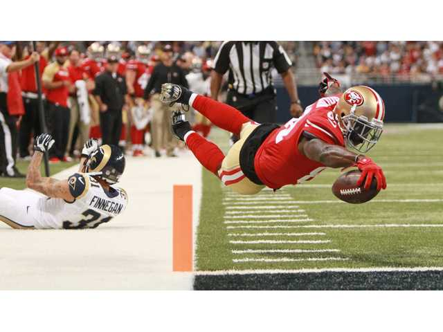 San Francisco 49ers wide receiver Anquan Boldin dives into the end zone to score on 20-yard touchdown reception as St. Louis Rams cornerback Cortland Finnegan defends Thursday in St. Louis.