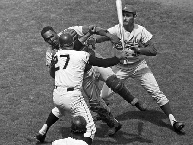 The Dodgers-Giants rivaly dates back to 1938. Above, In 1965 SF Giants Juan Marichal (27) swings a bat at L.A. Dodgers John Roseboro as Sandy Koufax, right, tries to break it up.