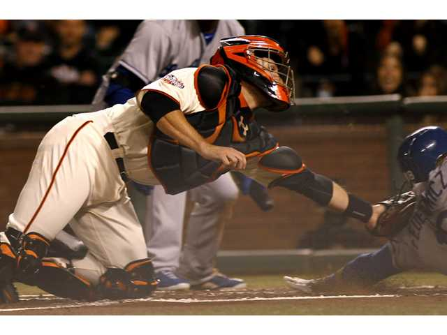 San Francisco Giant Buster Posey, left, tags out Los Angeles Dodger Tim Fedorowicz, right, in San Francisco on Thursday.