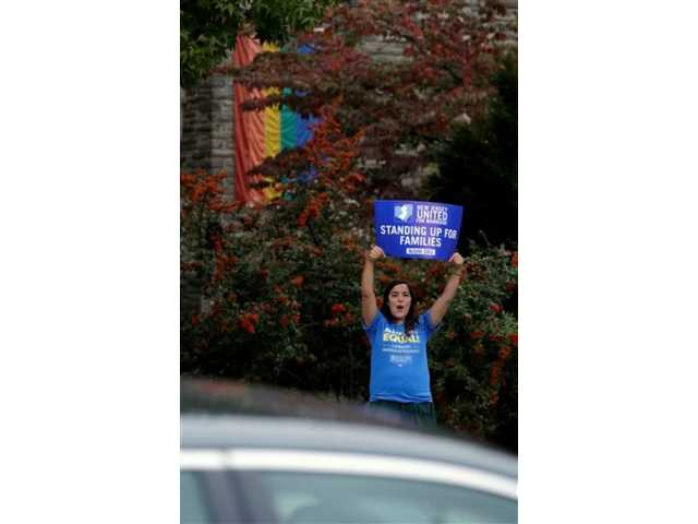 Alex Nikazmerad, 24, of North Plainfield, N.J., shouts at a vehicle passing by while holding a sign in front of First Congregational Church in Montclair, N.J., hours after same-sex marriages were made legal by a state judge, Friday.
