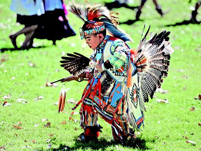 Sam Sierra, 8, wearing a porcupine hair roach and red tailed hawk wing fan, traditional of Northern Plains regalia participates in the Round Dance during the 20th Annual Hart of the West Pow Wow held at William S. Hart Park in Newhall on Saturday. Signal photo by Dan Watson