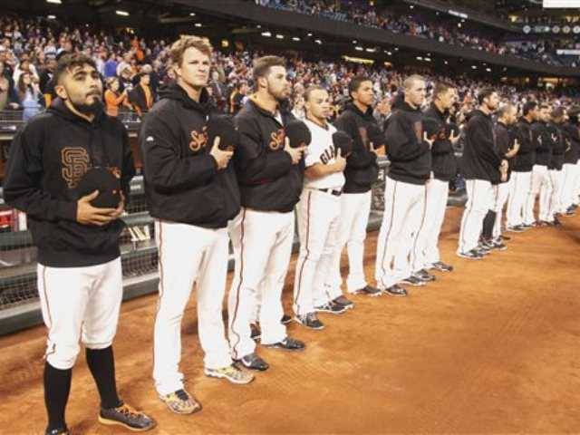 San Francisco Giants observe a moment of silence before a baseball game aganist the Los Angeles Dodgers, Thursday, Sept. 26, 2013, in San Francisco, in memory of a man who was fatally stabbed after a Dodgers-Giants game on Wednesday, not far from At&T Park.