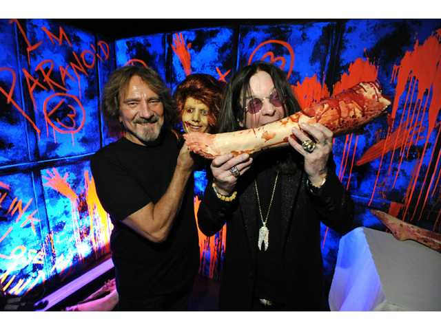 "In this Sept. 17 photo, Geezer Butler, left, and Ozzy Osbourne pose with props at the ""Black Sabbath: 13 3D"" maze at Universal Studios Halloween Horror Nights in Universal City."